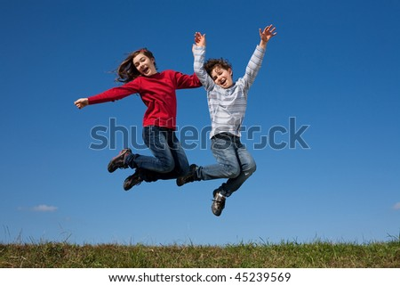 Kids jumping outdoor against blue sky - stock photo