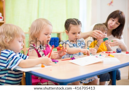 kids learning arts and crafts in kindergarten with teacher - stock photo