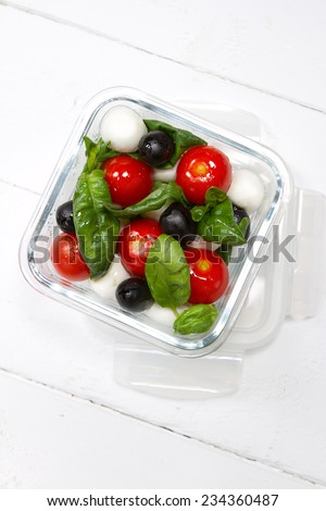 Kids lunch box: cherry tomatoes, olives, mozzarella, basil and olive oil - stock photo