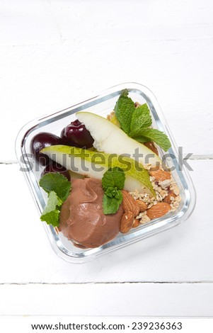Kids lunch box: chocolate ricotta, pear, muesli with almonds,��� unpitted cherry and mint - stock photo