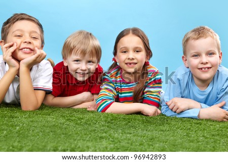 Kids lying on grass, resting and enjoying the weather - stock photo