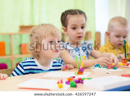 kids modeling or playing in kindergarten with interest. Children in day care centre. - stock photo