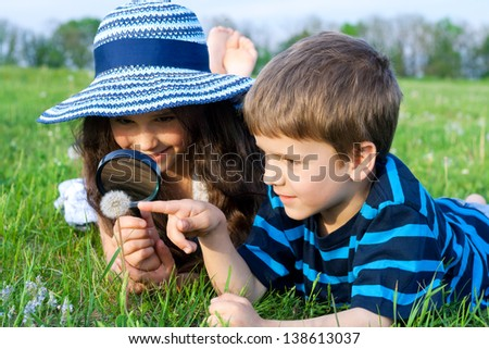 Kids on the meadow looking to dandelion with a magnifying glass - stock photo