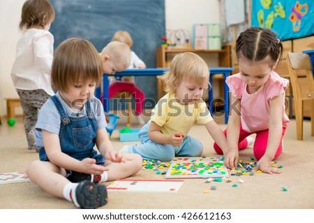 kids or children playing mosaic game in kindergarten room - stock photo