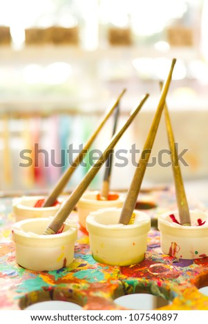 Kids paint pots on paint splattered table - stock photo