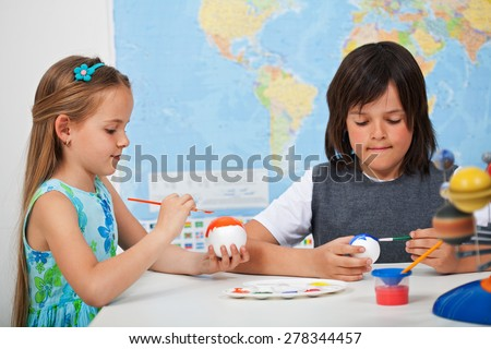 Kids painting the planets in art and science class - for a solar system scale model- focus on the girl face - stock photo