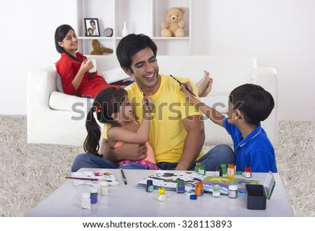 Kids painting their father - stock photo