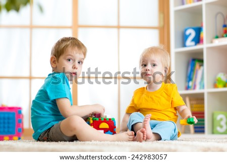 kids play together with educational toys in nursery - stock photo