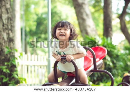 Kids playing at the see-saw in the playground - stock photo