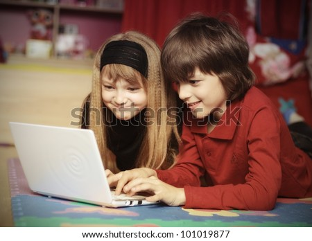 Kids playing computer game together at home - stock photo