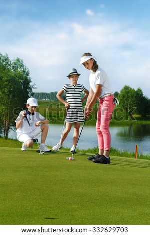 Kids playing golf by putter on green - stock photo
