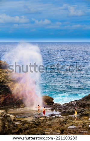 Kids playing in a blow hole with water spraying created from Pacific Ocean waves hitting the tall rocky cliff coastline made of lava on Maui, Hawaii, USA - stock photo
