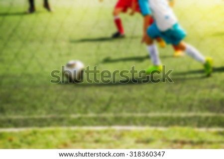 Kids playing soccer, attacker running with ball, defocussed blur sport background image - stock photo