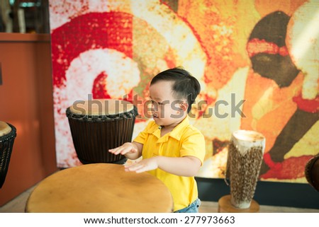 Kids playing traditional music instruments in the museum. Asian oy is curious and like to learn more knowledge. - stock photo