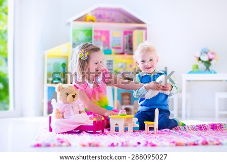 Kids playing with doll house and stuffed animal toys. Children sit on a pink rug in a play room at home or kindergarten. Toddler kid and baby with plush toy and dolls. Birthday party for little child. - stock photo
