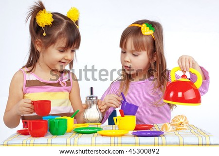 Kids playing with plastic tableware - stock photo
