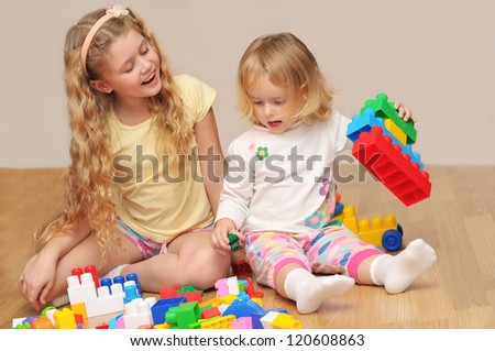 Kids playing with wooden blocks laying on the floor in their room - stock photo