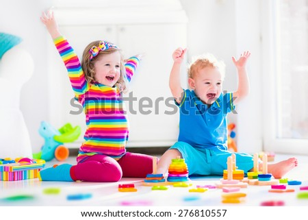 Kids playing with wooden toys. Two children, cute toddler girl and funny baby boy, playing with toy blocks, building towers at home or day care. Educational child toys for preschool and kindergarten. - stock photo