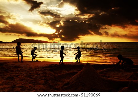 Kids plying on the beach - stock photo