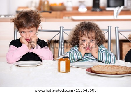 Kids pouting in the kitchen - stock photo
