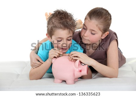 Kids putting coins in a piggy bank - stock photo
