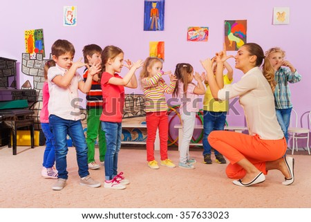 Kids repeat after teacher gesture in class - stock photo
