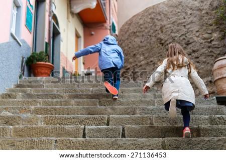 Kids running upstairs at street of colorful Manarola village, Cinque Terre, Italy - stock photo
