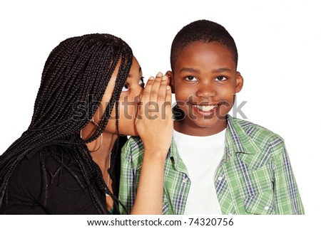 Kids sharing secret with grinning boy - stock photo