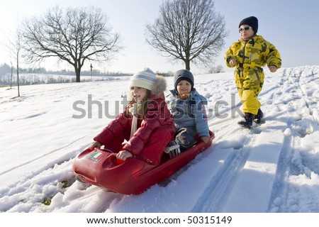 Kids sliding in the snow. - stock photo