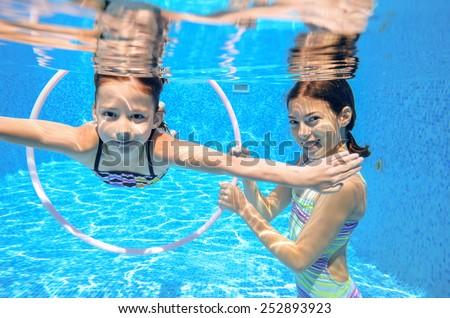 Kids swim in pool underwater, girls swimming, playing and having fun, children water sport  - stock photo