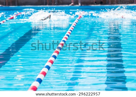 Kids swim meet in outdoor pool during the summer. - stock photo