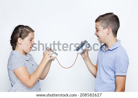 Kids talking to a can against gray background - stock photo
