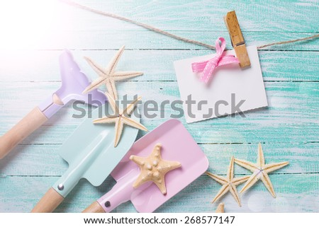 Kids tools for playing in sand  and sea objects in ray of light on turquoise  painted wooden planks. Place for text. Vacation, holiday, summer background. - stock photo