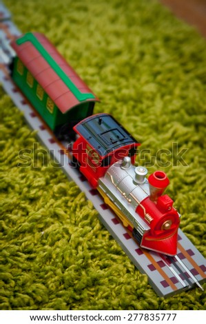 Kids toy train and toy railway on green carpet  - stock photo