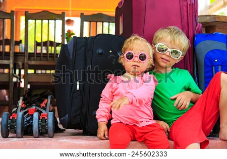 kids travel concept- little boy and toddler girl sitting on suitcases ready to travel - stock photo