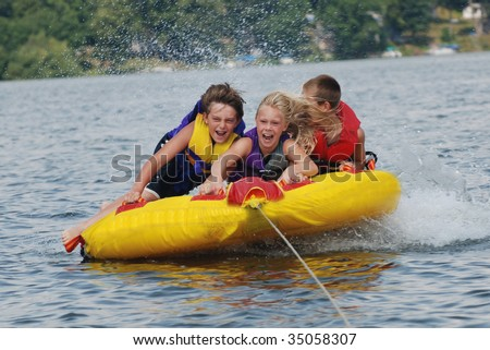 kids tubing fast behind boat - stock photo