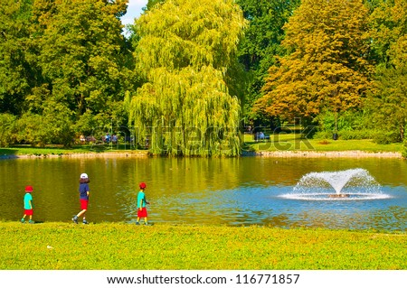 Kids walking at fountain in park - stock photo