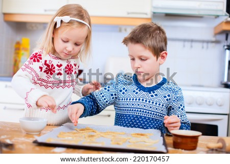 Kids wearing warm sweaters baking cookies in house kitchen on winter day - stock photo