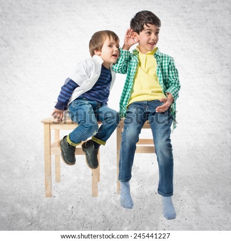Kids whispering over textured background  - stock photo