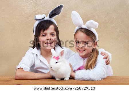 Kids with bunny ears holding their favorite pet - a white rabbit - stock photo