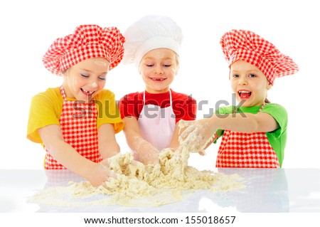 Kids with chef hats preparing tha cake dough - stock photo