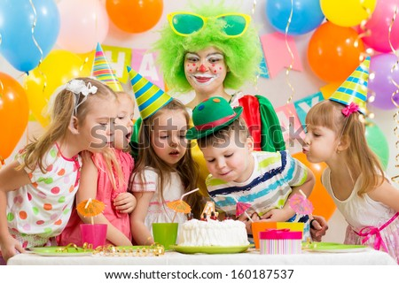 kids with clown celebrating birthday party and blowing candle on cake - stock photo