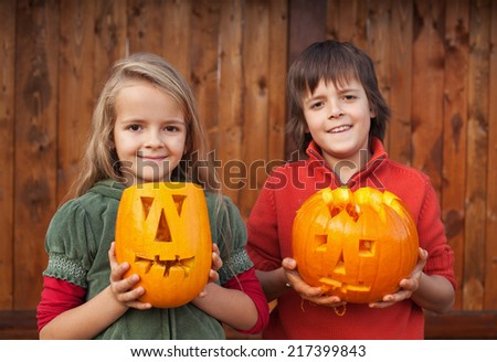 Kids with freshly carved Halloween pumpkin jack-o-lanterns - stock photo