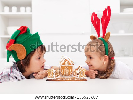 Kids with funny christmas hats looking at gingerbread house - stock photo