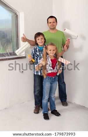 Kids with their father preparing to paint the room in their new home - redecorating concept - stock photo