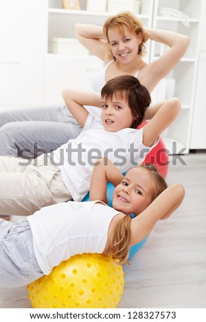 Kids with their mother doing gymnastic exercises with large balls at home - stock photo