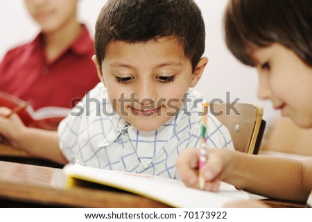 Kids working schoolwork in the school, classroom, togetherness - stock photo