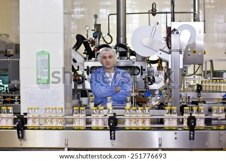 Kiev region, UKRAINE - 15 November 2014: Dairy baby food factory. Worker conducts quality control at conveyor belts - stock photo