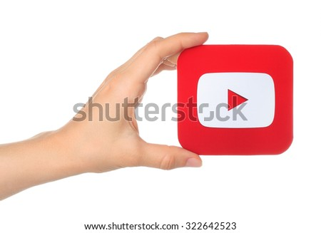 Kiev, Ukraine - August 18, 2015: Hand holds YouTube icon printed on paper on white background. YouTube is a video-sharing website - stock photo