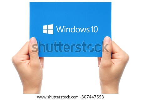 KIEV, UKRAINE - AUGUST 18, 2015:Hands hold Windows 10 logotype printed on paper. Windows 10 is an operating system developed by Microsoft. - stock photo